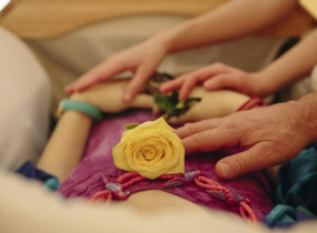 People laying hands on a woman's body, who is holding a yellow rose.